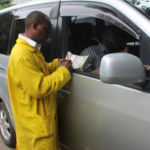 A parking attendant issues a receipt to a motorist in Nairobi. www.businesstoday.co.ke