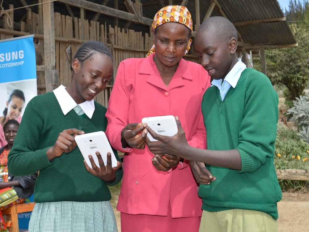 Pupils of Kampi Primary School in Nyeri County show a parent how tablets work. Airtel Kenya as offered free internet access to students to continue learning as coronavirus forces a lock down on many aspects of life. www.businesstoday.co.ke