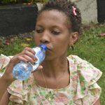 A young woman drinking bottled water www.bisinesstoday.co.ke
