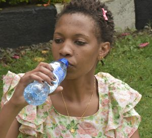 A young woman drinking bottled water www.bisinesstoday.co.ke