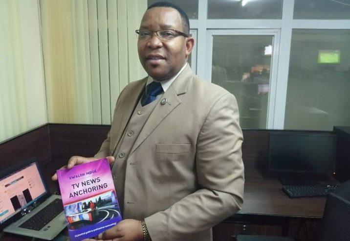 Swaleh Mdoe displays a copy of his book www.businesstoday.co.ke