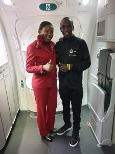 World marathon record holder Eliud Kipchoge poses for a photo with a KQ air hostess after landing in the country. Photo/ Kenya Airways