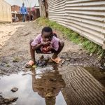 A child takes water from a puddle in a slum. Despite the increased suffering among Kenyans, the World Bank thinks Kenyans are less poorer than they were 4 years ago. www.businesstoday.co.ke