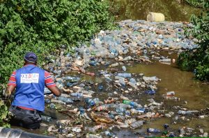 Dumpsite in Nairobi - A volunteer cleaner wades through a batch of plastic trash floating in River Njoro Nakuru Kenya www.businesstoday.co.ke