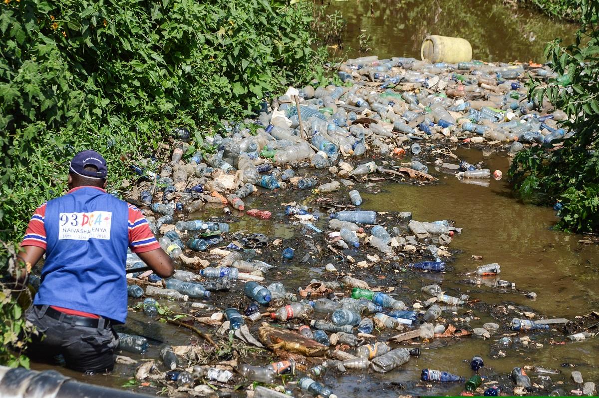 Dumpsite in Nairobi - A volunteer cleaner wades through a batch of plastic trash floating in River Njoro Nakuru Kenya www.businesstoday.co.ke
