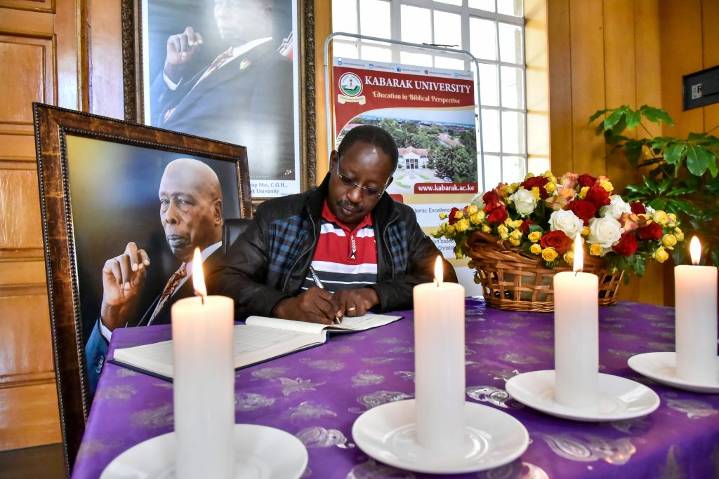 David Namu signibusinesstoday.co.keng the visitors book against the backdrop of the iconic photo he took of the late President Daniel Moi at Kabarak. Namu was one of the late president's favourites covering his events. www.