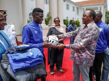 President Kenyatta gives a signed ball to AFC Leopards captain Robinson Kamura while Sports CS Amb. Amina Mohamed looks on. www.businesstoday.co.ke