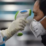 A medical staff member takes the temperature of a man at the Wuhan Red Cross Hospital in China on Jan. 25. The WHO is concerned about the HIV positive and malnourished children as the virus spreads. www.businesstoday.co.ke