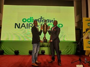 FKF President Nick Mwendwa (left) with Odibets country manager Aggrey Sayi showcase the Odi Mtaani cup. www,businesstoday.co.ke