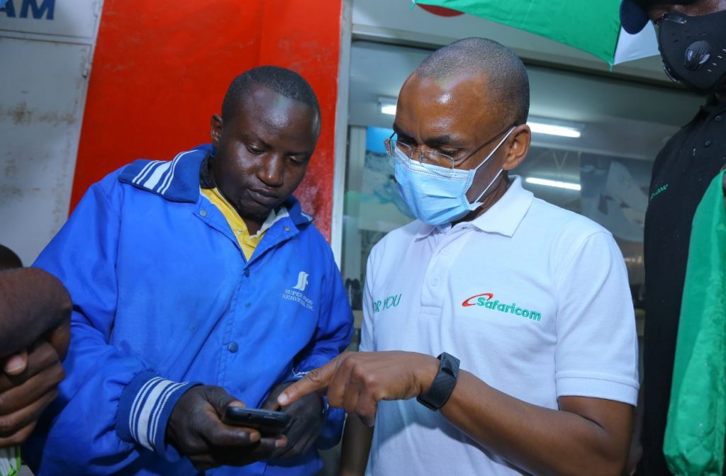 Safaricom PLC CEO Peter Ndegwa is taken through a Lipa Na M-PESA process by Alexander Ondenyi a fruit vendor in Kakamega town during his visit in the town
