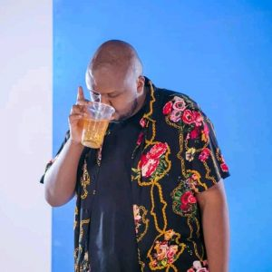 Mejja drinks out of a tumbler at a past video shoot