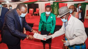 President Uhuru Kenyatta handing over a title deed to a member of the Samburu community as Lands Cabinet Secretary Farida Karoney looks on at a past function.