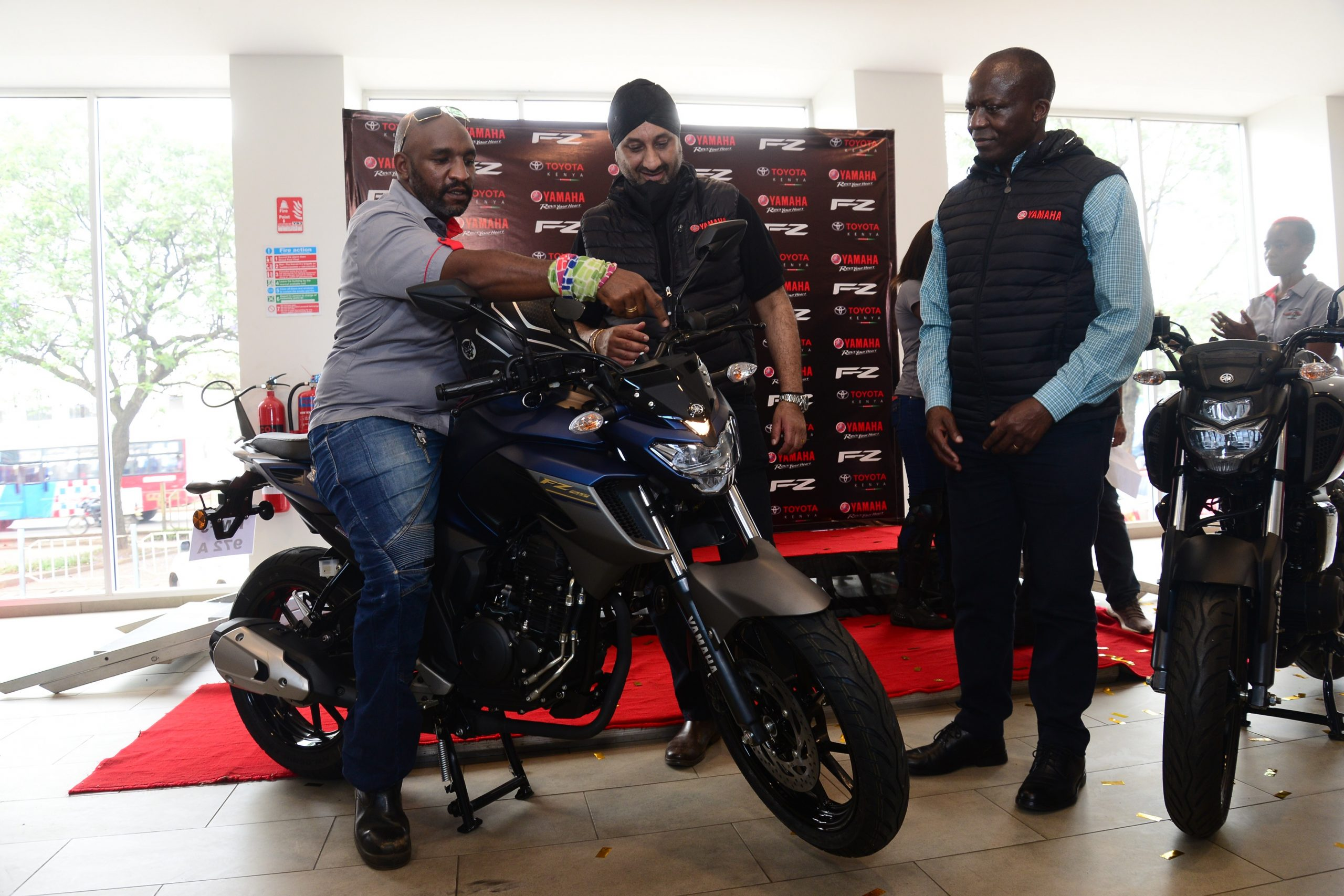 Motorcycle Kenya Vice Chairman, David Mbaya (left), is guided in testing some of the features of the newly launched Yamaha FZ25, 249-cc motorcycle by Toyota Kenya Managing Director, Arvinder Reel (centre) and the Chief Operating Officer, Joshua Anya.