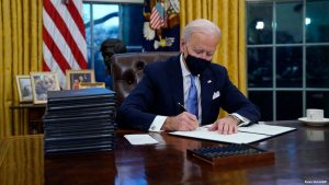 United States President Joe Biden signing executive orders on his first day in office on January 20, 2021