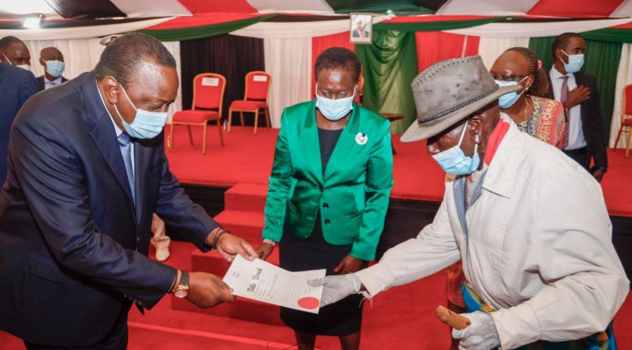 President Uhuru Kenyatta hands over a title deed to a member of the Samburu community on November 4, 2020 as Lands Cabinet Secretary Farida Karoney looks on during a ceremony in Nairobi.
