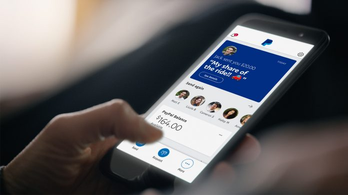 A PayPal user looks at the mobile app on their smartphone. Kenyan users of the payments service, mostly freelancers, are up in arms over its controversial holding of payments.