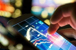 A trader looks at charts on their mobile device