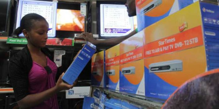 A customer looks through StarTimes decoders at a retail outlet.