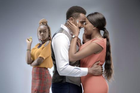 elina cast members Nelson (Pascal Tokodi) and Selina (Celestine Gachuhi) embrace each other as Chichi (Azziad Nasenya) looks on.