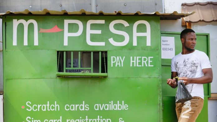 A man walks by an M-Pesa agent outlet in Nairobi. Calls are growing for M-Pesa agents to be recognized as Safaricom employees.