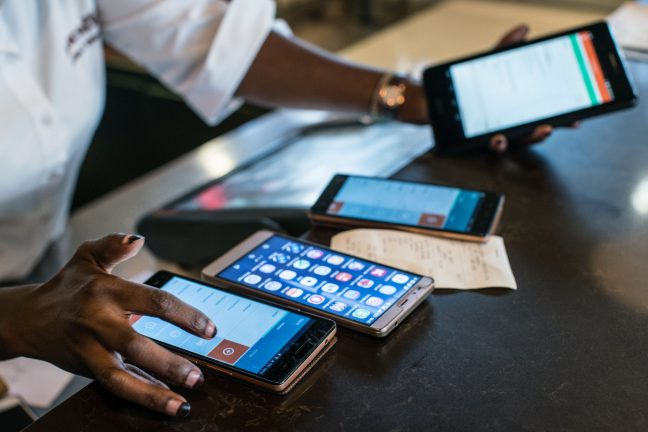 A person using multiple smart phones at the same time. The cost of transactions on mobile money services such as M-Pesa has many Kenyans looking for cheaper ways to send money and make payments.
