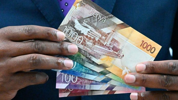 A man holding up Kenyan bank notes. The government is considering introducing a Wealth Tax to shore up revenues.