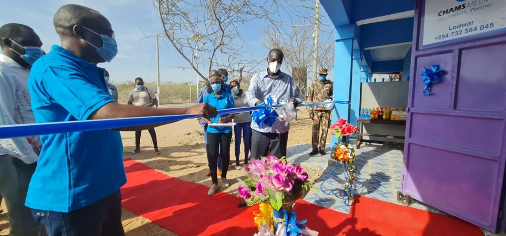 Alex Chamwada (left) and Turkana Governor Josphat Nanok cut the ribbon to officially open Chams Media regional office in Lodwar on March 24, 2020. Chamwada, a former Citizen and KTN journalist, went from the newsroom to running his own media empire.
