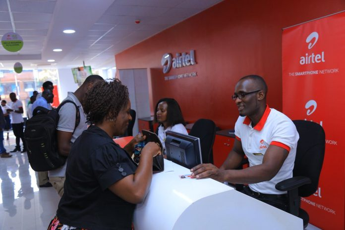 Airtel representatives serve customers at a store. Airtel Kenya will be required to comply with local ownership regulations by 2024.