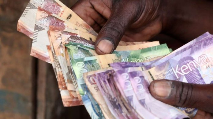 A trader counting money after a day's sales. Defaults on mortgages and loans issued to the transport sector crossed the Ksh100 billion mark - a worrying indicator of tough economic times since the onset of the pandemic.
