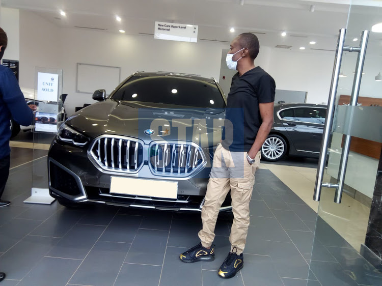 Maina Kageni standing next to his 2020 BMW X6. His collection includes several other high-end cars. [Photo/ The Star]