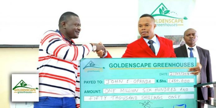 Goldenscape Director Peter Wangai Muriithi (in red) hands over a dummy cheque before he was accused of defrauding investors hundreds of millions of shillings. [Photo/ Goldenscape Greenhouses]