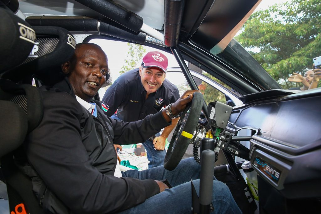 Equator African Rally Championship (ARC) winner, Carl Tundo (RIGHT) gives Safaricom PLC, Chief Financial Service officer, Sitoyo Lopokoiyit (LEFT) a tour of the interior part of his rally car during the Safaricom WRC sponsorship of Carl Tundo in Naivasha.