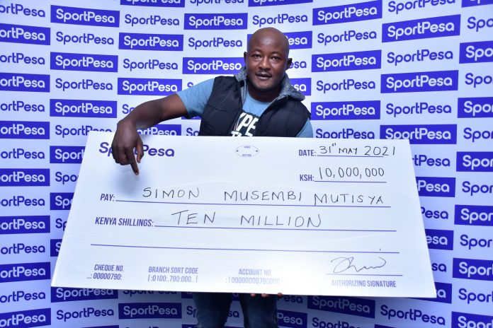 SportPesa Midweek Jackpot winner Simon Musembi, a Machakos based shoe hawker all smiles as he receives his cheque