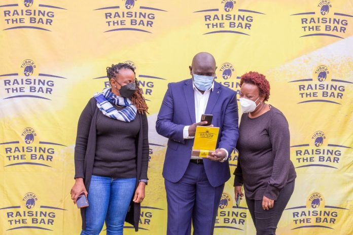 EABL Commercial Director Joel Kamau with KBL's Head of Sales - Nairobi scans a Drink IQ QR code. With him are Yvonne Mwangi and Phoenix Bar & Grill Director Wambui Guchu.