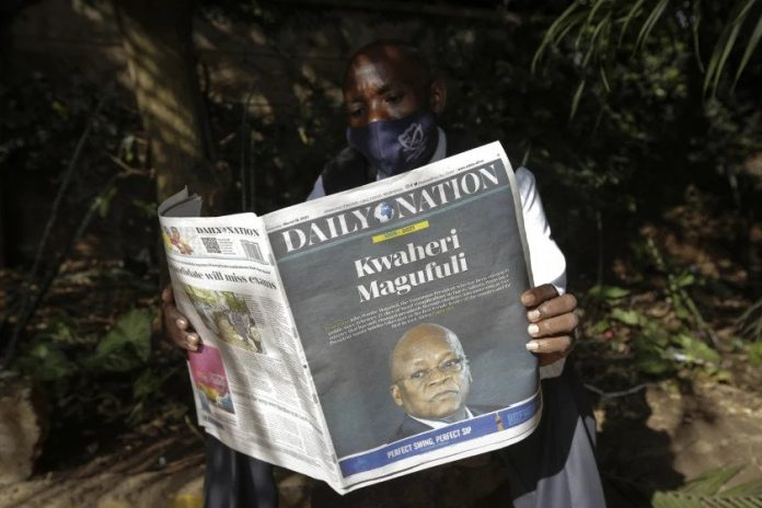 A man in Nairobi reads the Daily Nation on March 18, 2021. Print which has been NMG's traditional cash cow continued its recovery from the pandemic induced decline of 2020 in the first half of 2021. [Photo/ AP Photo/Khalil Senosi]