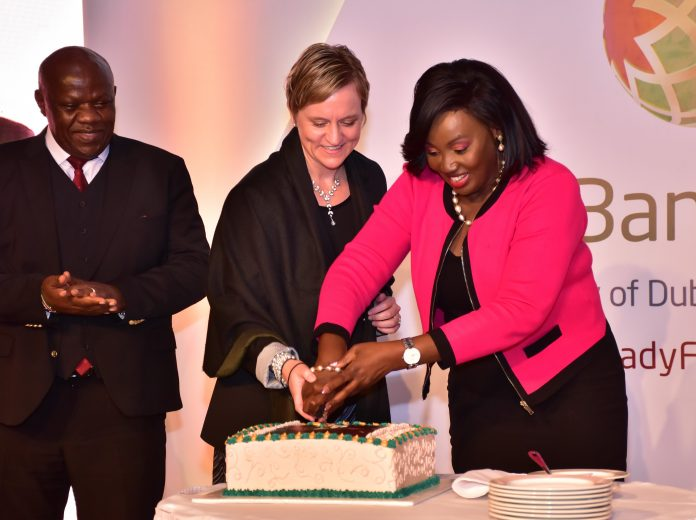Treasury CAS Eric Wafukho (L) looks on as DIB Bank Kenya Board of Director Alison Blignault (C) and KNCCI Vice Chair Women in Business Nancy Muthoni cut a cake to mark the bank's 4 years Anniversary
