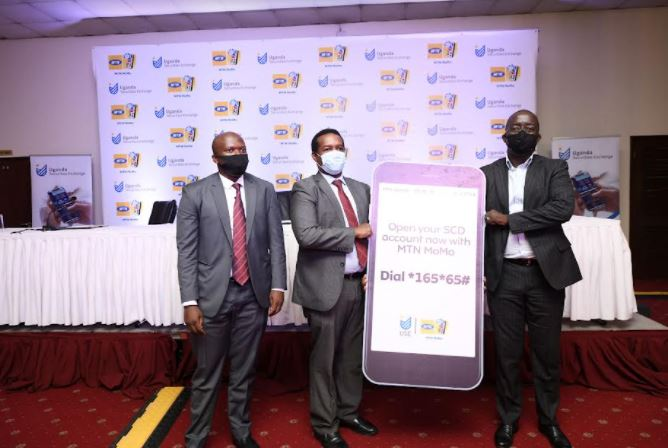 Mr Bob Musinguzi, Manager SCD-USE (l),Paul Bwiso, the Chief Executive Officer, Uganda Securities Exchange (c) pose for a photo alongside Mr. Stephen Mutana,(r) the Chief Executive Officer MTN Mobile Money Limited during the launch of the digital Securities Central Depository (SCD) account opening platform in Kampala